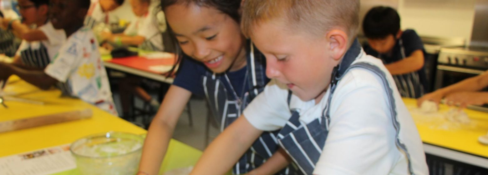 two small children kneading dough in cooking class