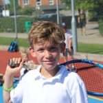 young boy posing for a photo with a tennis racket