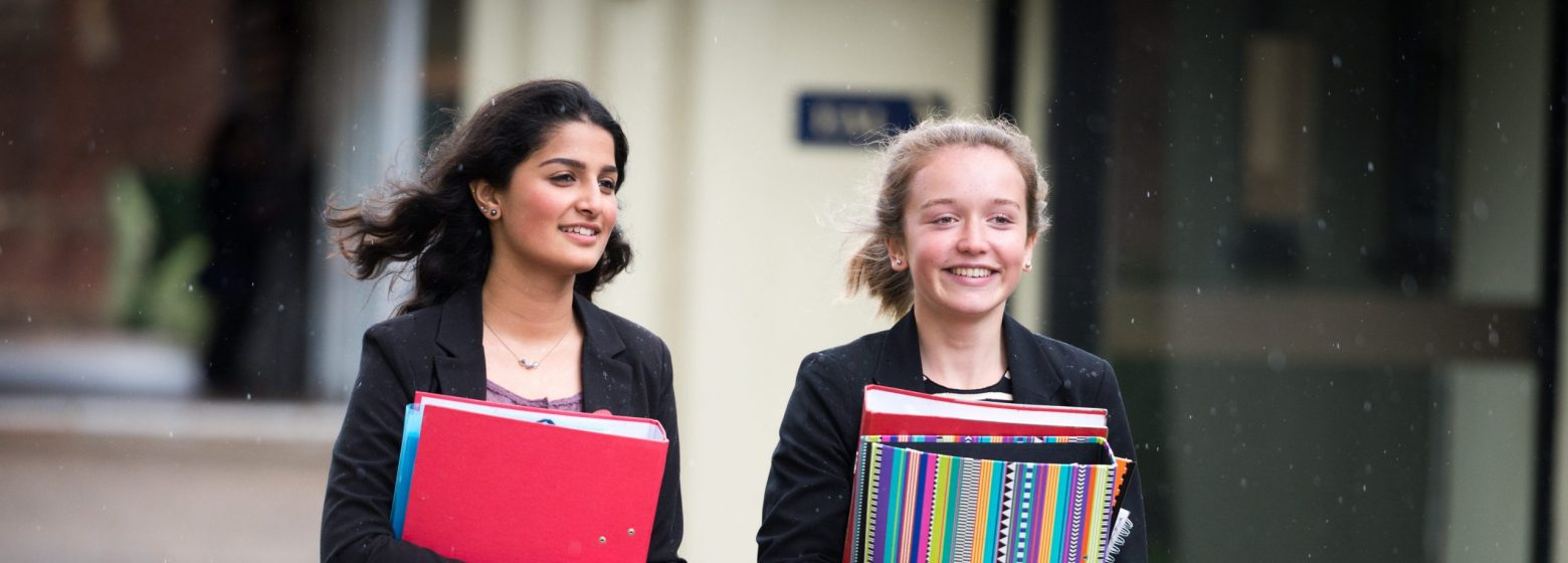 two students walking and carrying folders and books