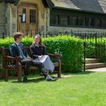 girl and boy sitting on a bench in their school uniform