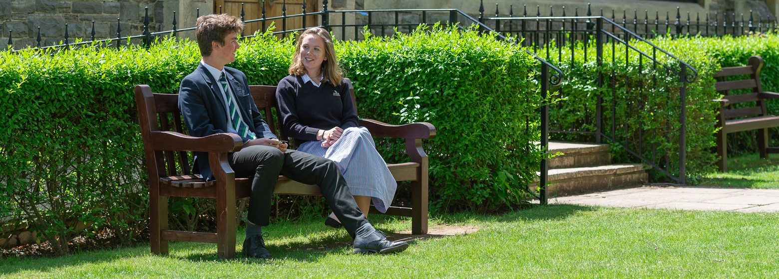 girl and boy sitting on a bench in their school uniform