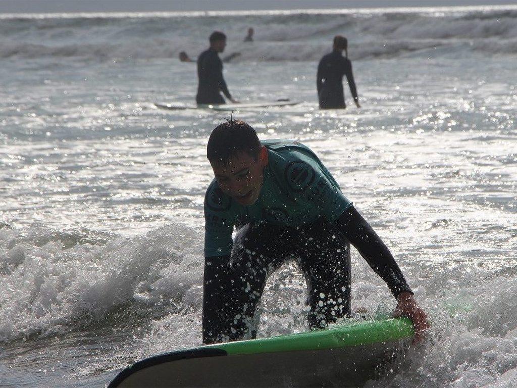 Teenage Boy in Sea Holding a Surf Board