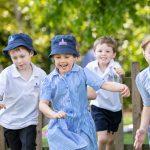 Children running across the playground in their uniforms
