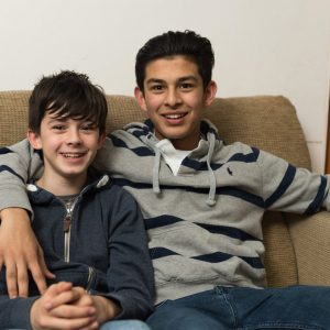 two boys sitting on sofa