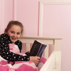 girl in pink bed reading