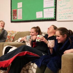 4 girls relaxing on sofa drinking hot drinks