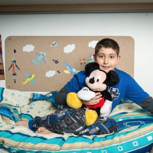 boy with mickey mouse plush in bed