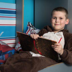 boy in onesie writing in journal