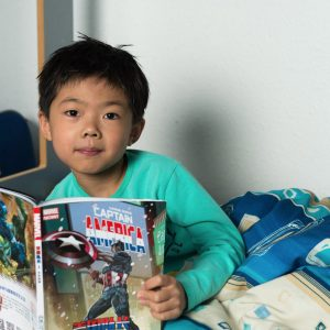 boy reading a comic book in bed