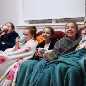 girls covered with blankets with mugs