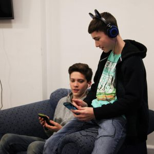 boys with headphones looking at mobile phones