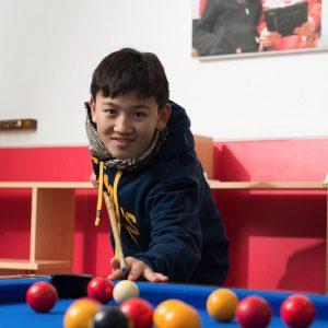 boy playing pool