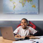 school boy working on laptop