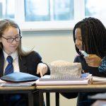 two girls writing in classroom