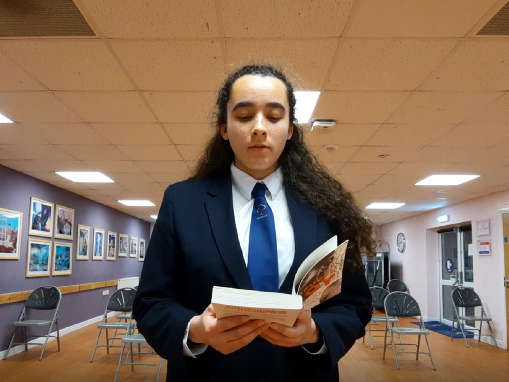 student preparing for the debating competition by reading a study book